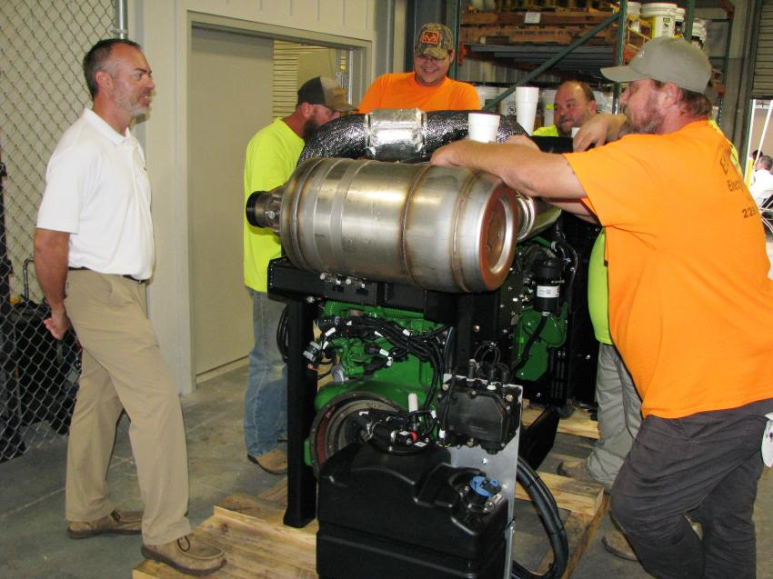 Providing more info on a John Deere Power Systems engine on display is Jason Scott (L), Flint Power Systems Division regional sales manager.