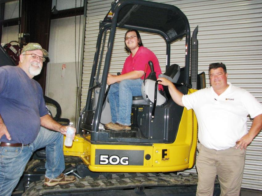 (L-R): Checking out a Deere mini-excavator inside the facility are Robert Walker and Daniel Walker of Walker Septic Tank and Excavating, Pinetta, Fla.; and Jim Rodgers, Flint-Valdosta.
