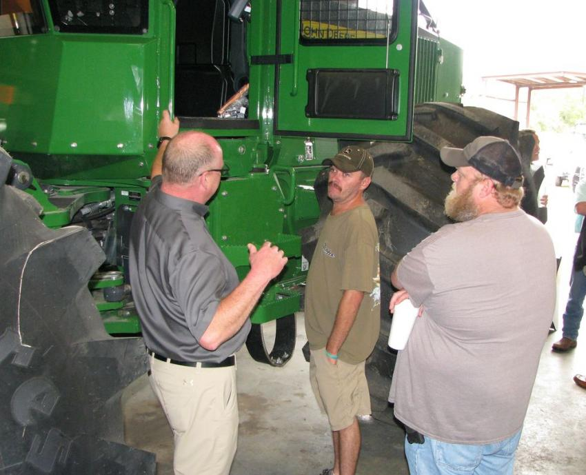 (L-R): John Deere Forestry's Paul Holman goes over some of the product upgrades incorporated into the new John Deere 648L-II log skidder with T.J. McCall and Joe Bennett of J&J Logging of Valdosta, Ga.