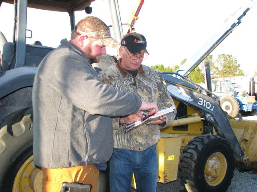 Justin Cain (L) of South Georgia Land Investments, Hahira, Ga., and Rodney Cain of Cain Plantation Estates, also in Hahira, Ga., look over their auction catalogues for additional info on several backhoe loaders of interest.