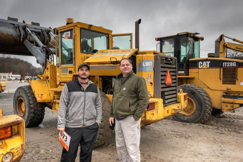 Wender Gomes (L) of Proscape Company and David Bruschi of Guardian Group Properties, both of Shrewsbury, Mass., are looking at a 1994 Volvo L90B integrated tool carrier.
