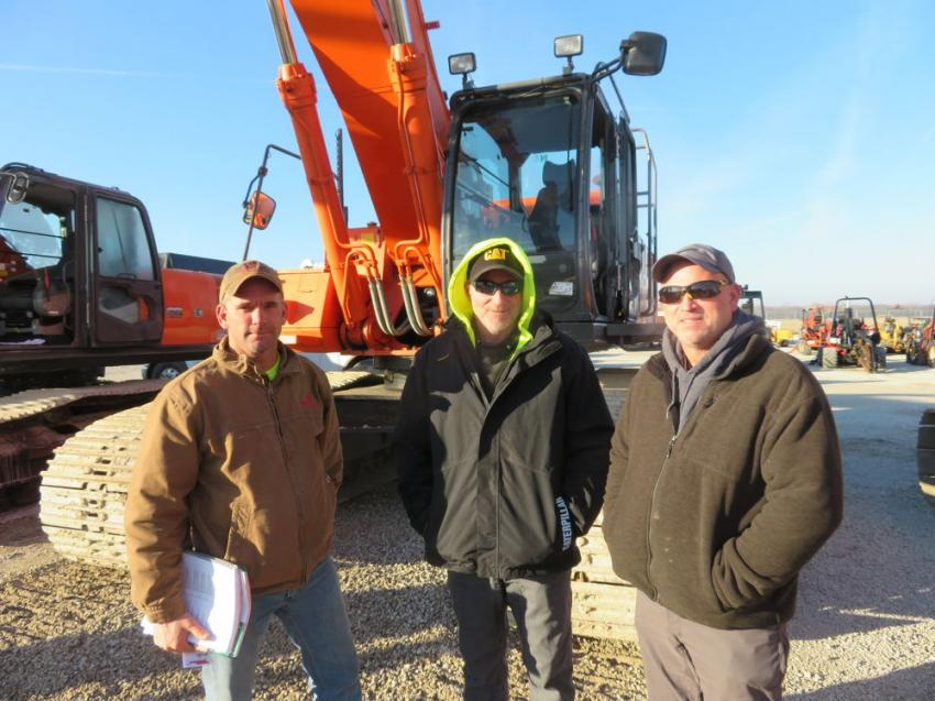 (L-R): Rick Parker and Brian and Dave Westwood, all of Midwest Equipment Group, stand in front of a Hitachi 450LC excavator.