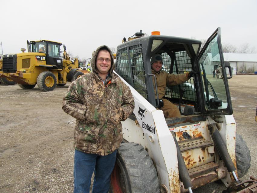 Eddie Burkholder (L) of Burkholder Transport and Ryan Zimmerman of RZ Excavating go over a Bobcat S250 skid steer loader.