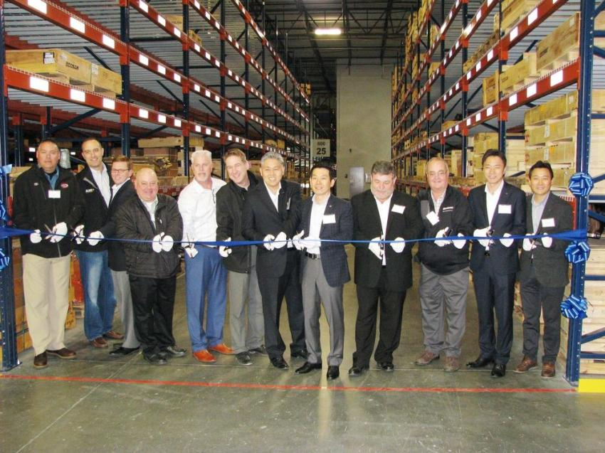 Doosan staff and some of the dealers in attendance prepare to cut the ribbon marking the official opening of the center.