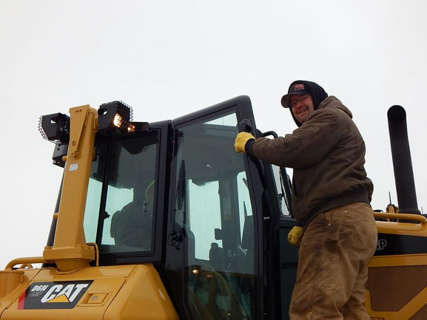 Jeremy Crull of R&K Construction, Evansville, Wis., checks out a Cat D6 dozer, which went to R&K for $50,000. Jeremy's father, Ralph Crull, is sitting in the dozer's cab.