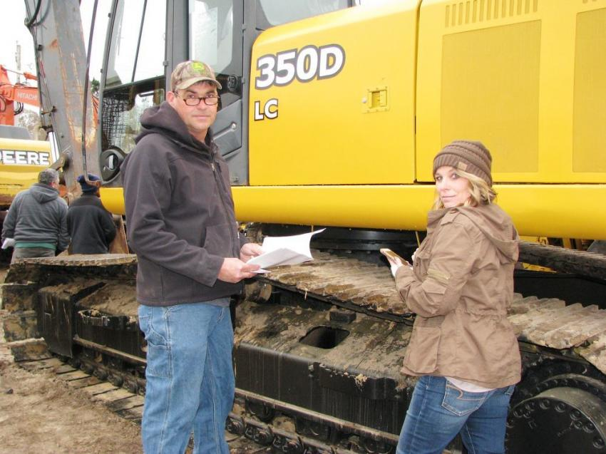 Discussing their thoughts on a Deere 350D LC about to go on the auction block are Russell Wood (L) and his wife, Tracy Wood, of Long Cane Land Clearing, Donalds, S.C.