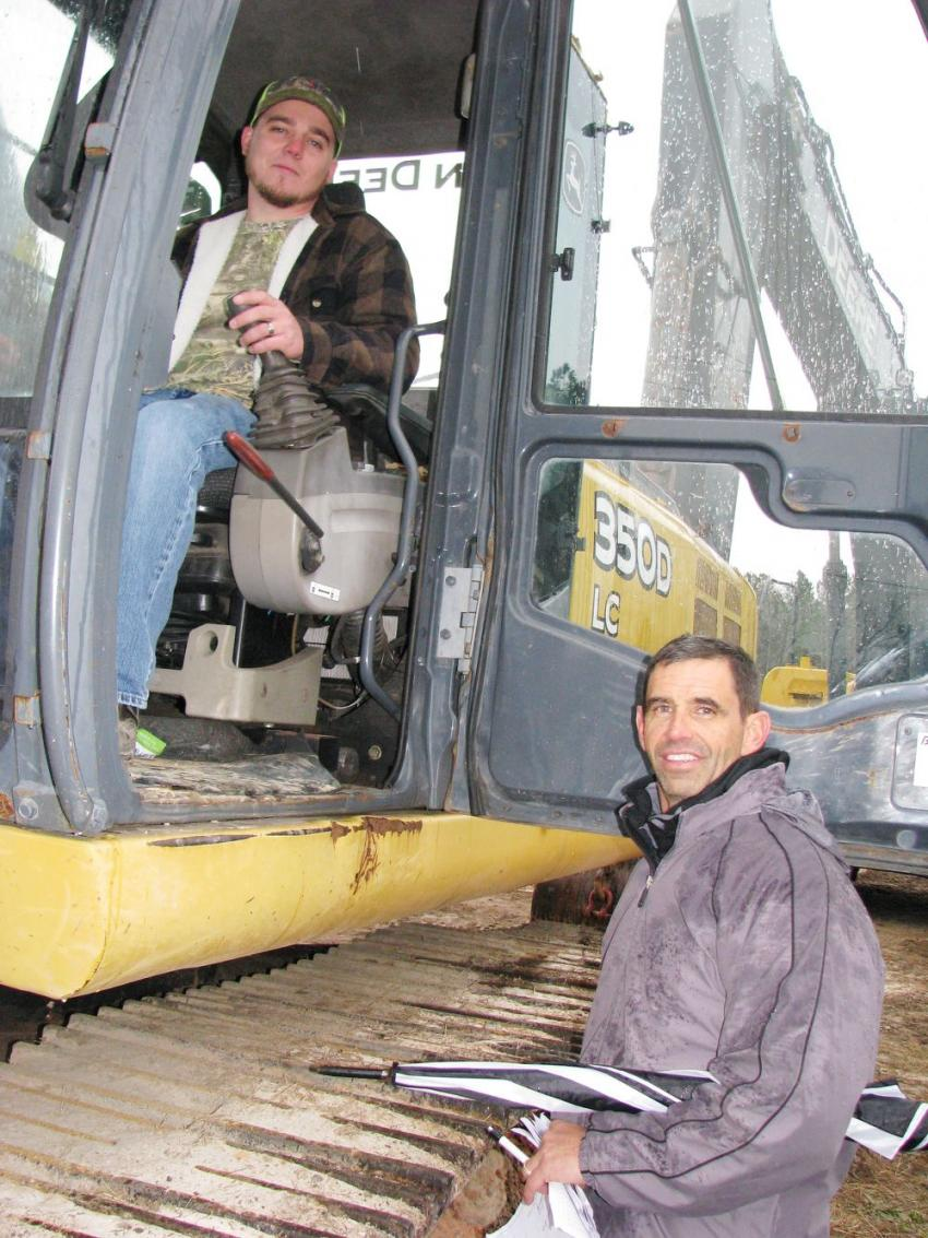 Contractors test-operating a Deere 350D excavator are Mike Sykes (in cab) and Bill Carmouche of Specialty Industrial, Baton Rouge, La.