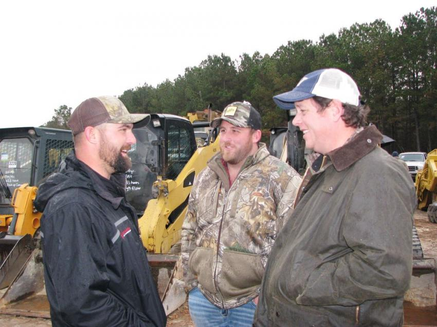 "Joey Martin Auctioneer's Thomas Davis Cox (L) and the ""Iron Legend"" himself, Tom Powell (R) talk with Kyle Borchers of Pro Pump Solutions, Cleveland, Ga., about the machines about to be auctioned."