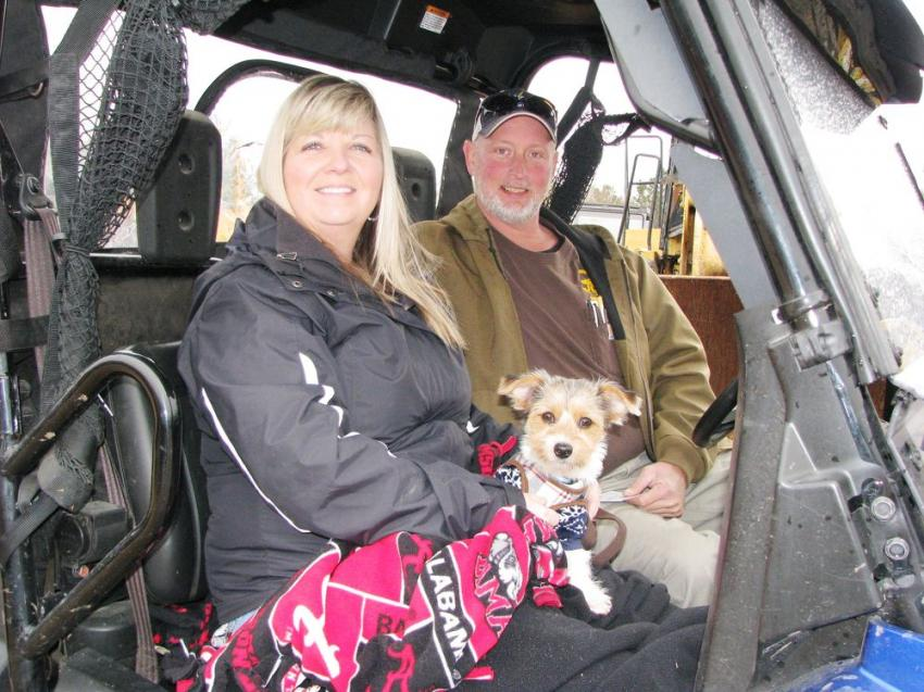 Cruising the auction lot in their Honda Pioneer four-wheeler are Missy Hargis (L), with her pup, DJ, and Jason Collins of Jason Collins Construction, Jasper, Tenn.