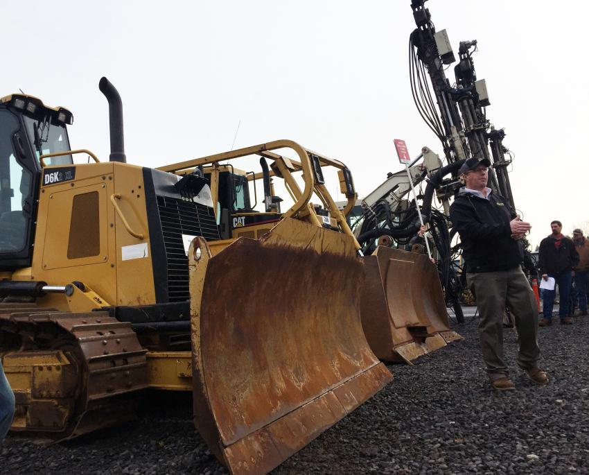 Ringman Dan Goss keeps track of who is bidding on the Cat D6R XL Series III crawler dozer at an auction in Spokane, Wash.