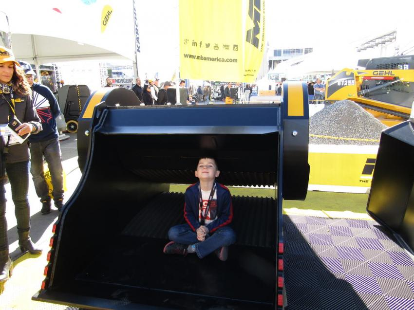 A young WOC attendee stops to rest in a MB America BF 120.4 crusher bucket.