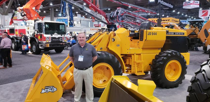 Chris Kline, John Deere product specialist, celebrates with the company's 50-year-old JD 544 wheel loader at World of Concrete.