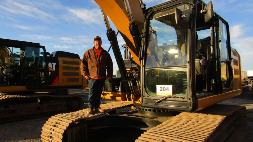Looking to take some equipment home for his engineering business in Lake Havasu, Ariz., David Evans thoroughly inspects this 2012 Cat 329EL hydraulic excavator before bidding starts.