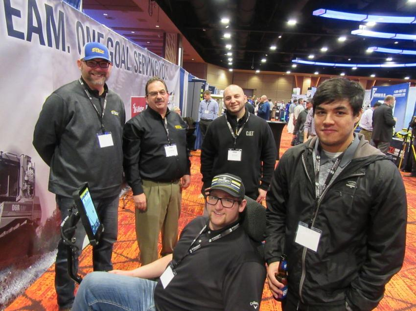 At Michigan Cat's booth, Blake Hammond of Ferris State University (seated) tries out a simulator along with Thomas Denver (R), also of Ferris State, while (L-R) Sitech Michigan's James Ludwig and Michigan Cat's John Miriani and Josh Brown discuss Caterpillar equipment.