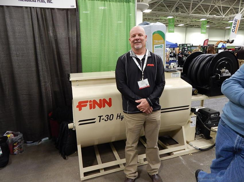 John Rabideaux, store manager of Trenchers Plus, Burnsville, Minn.,  stands in front of a Finn T-30 HydroSeeder.