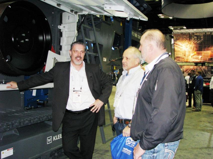 Evan Clarke (L), vice president of sales for Kleemann products, talks with guests about the Kleemann MOBIREX MR130 impact crusher on display in the Wirtgen Group display area.