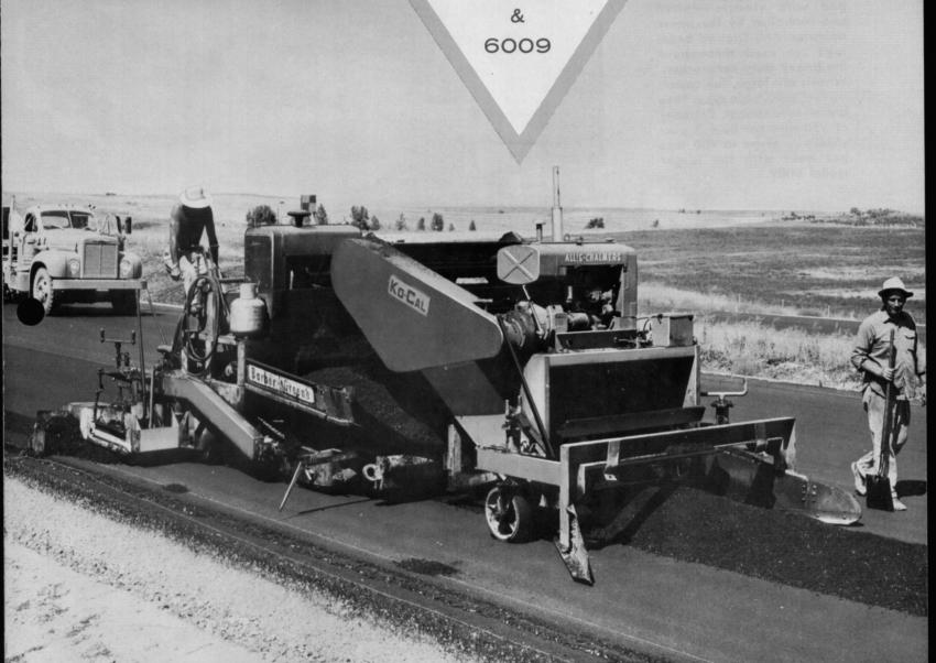 Working in material deposited by bottom dump trailers, a Ko-Cal windrow elevator charges a paver.