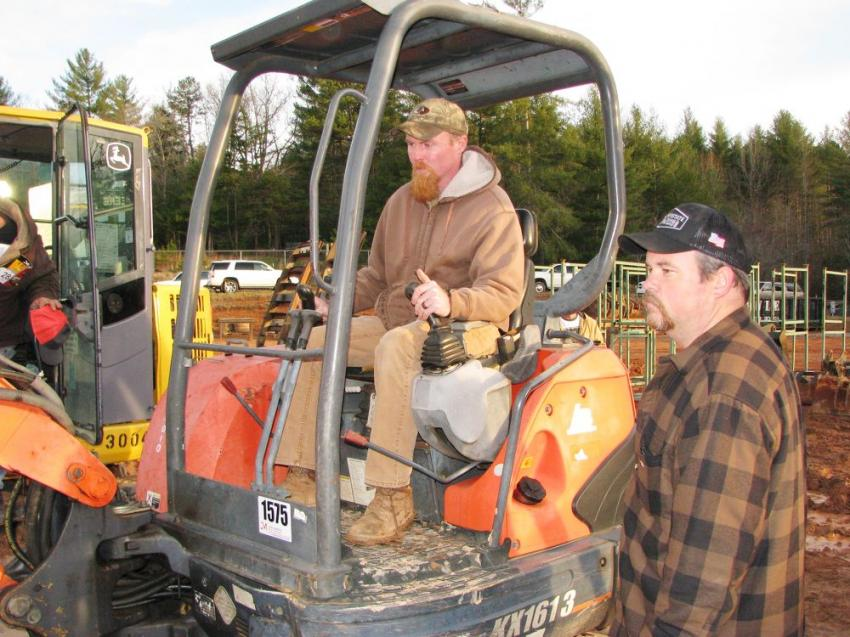 Tommy Worley (L) of K & A Construction,  Brasstown, N.C., and Jason Belcher of Hayesville, N.C., test-operate a Kubota KX161-3 mini-excavator.