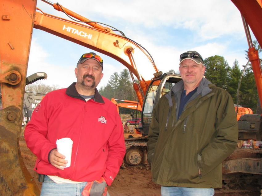 Joe Smith (L) of Smith Drilling Services, Monroe, Ga., and Kevin Thomas of International Construction Equipment, Matthews, N.C., look over some of the Hitachi excavators.