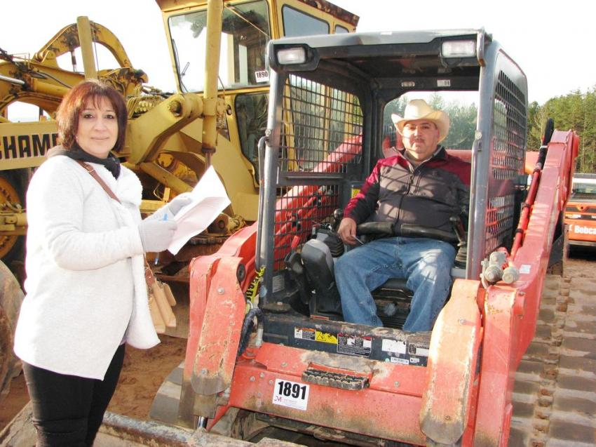 Maria Gonzalez (L) and Alfonso Gonzalez of AG Construction, Lawrenceville, Ga., were interested in a pair of Kubota SVL 90-2 compact track loaders that were about to go on the auction block.