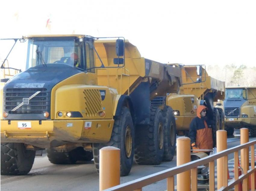 Volvo A40D artic trucks are ready for bids as they roll across the ramp.