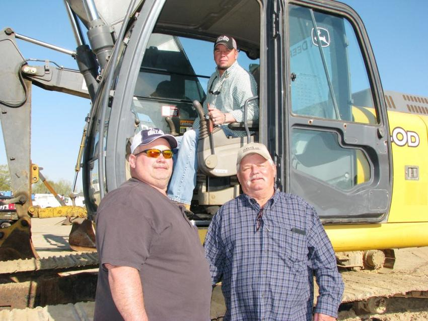 Looking over some of the hydraulic excavators in the sale line-up, including this John Deere 240D LC are Craig Davis (L), Warren Ballard and, up in the cab, Drew Elmore, all of Ballard Builders Inc., Winfield, Ala.