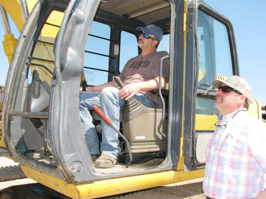 Checking out a Deere 120C are Sidney McClain (L) of S & S Equipment Sales, Houlka, Miss., and Mark Latham of Southern Equipment Sales, Finger, Tenn.