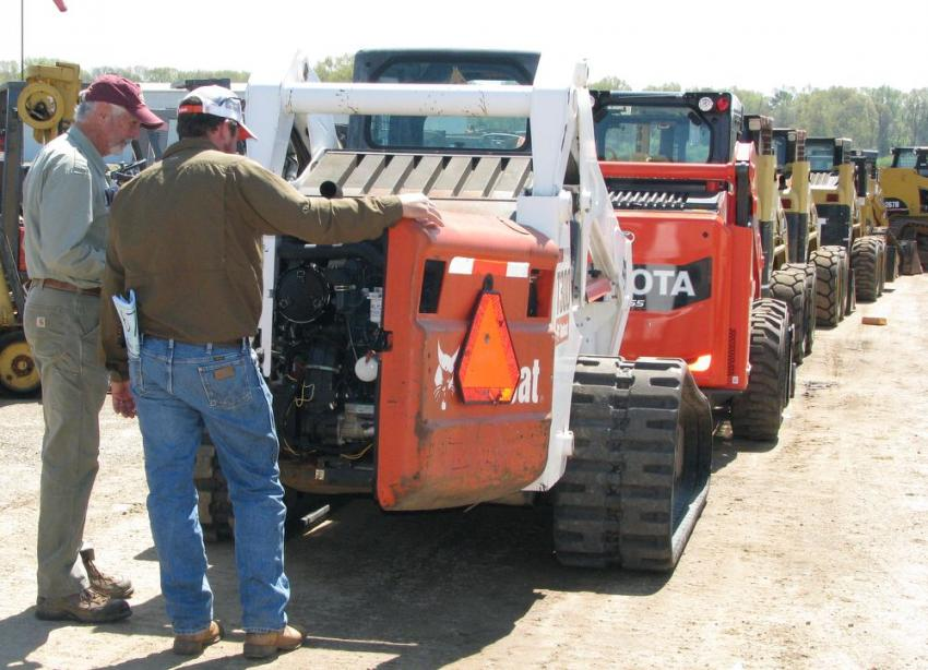 Bidders take a last-minute look at some of the compact track loaders lined up and ready to hit the ramp to be auctioned off.