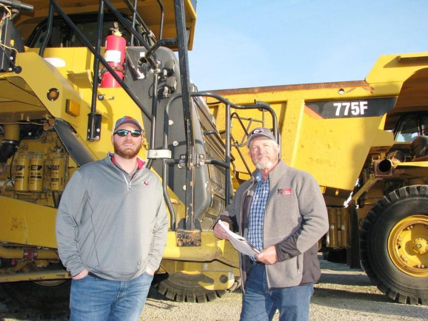 Admiring the big Cats, including a pair of 775F rigid-frame trucks, are Aaron Matthews (L) and Bob Matthews of Matthews Motors, Augusta, Ga.