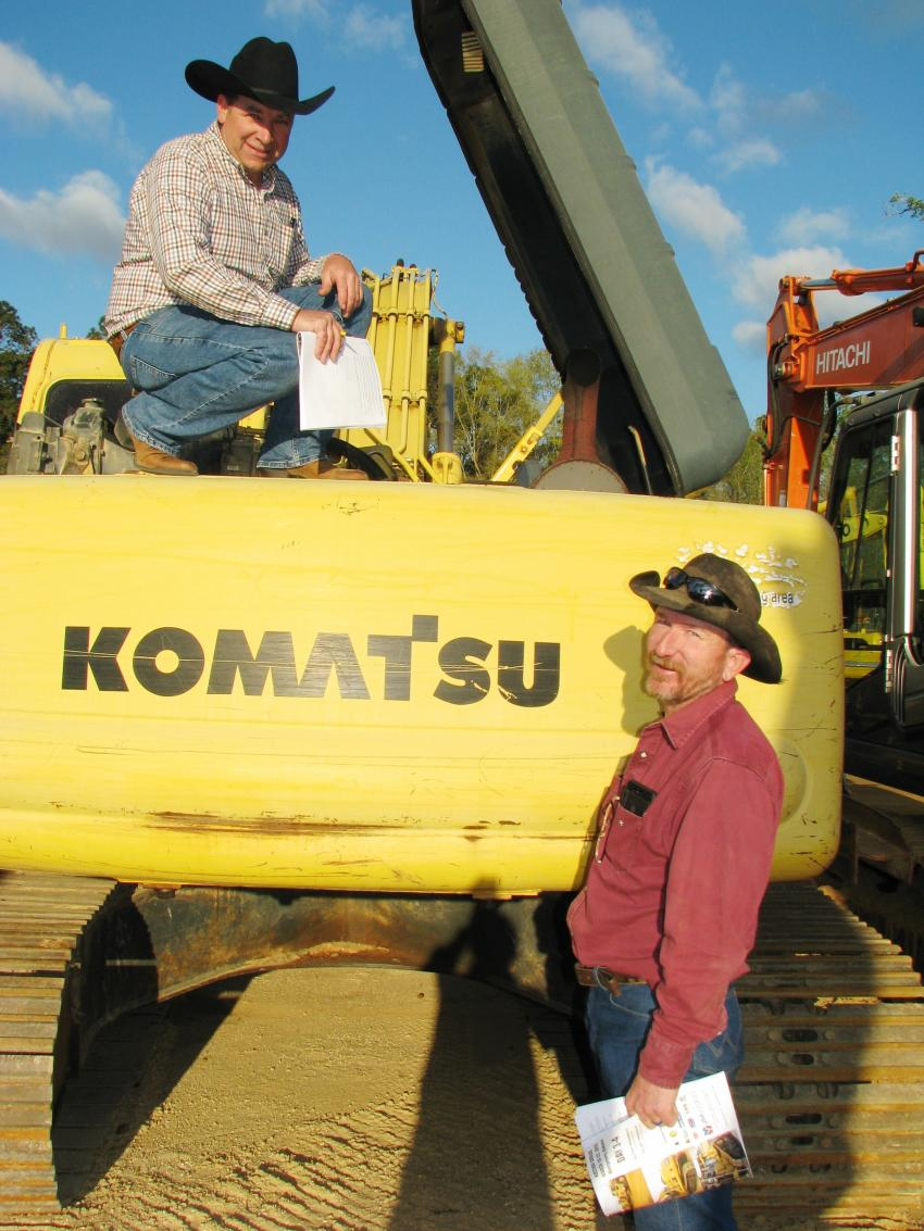 Inspecting the power plant of a Komatsu PC200LC are Daniel Nissley (L) of Nissley Equipment, Columbia, Ky., and Sud Danks of Chimney Rock Farms, Lewisburg, Ky.