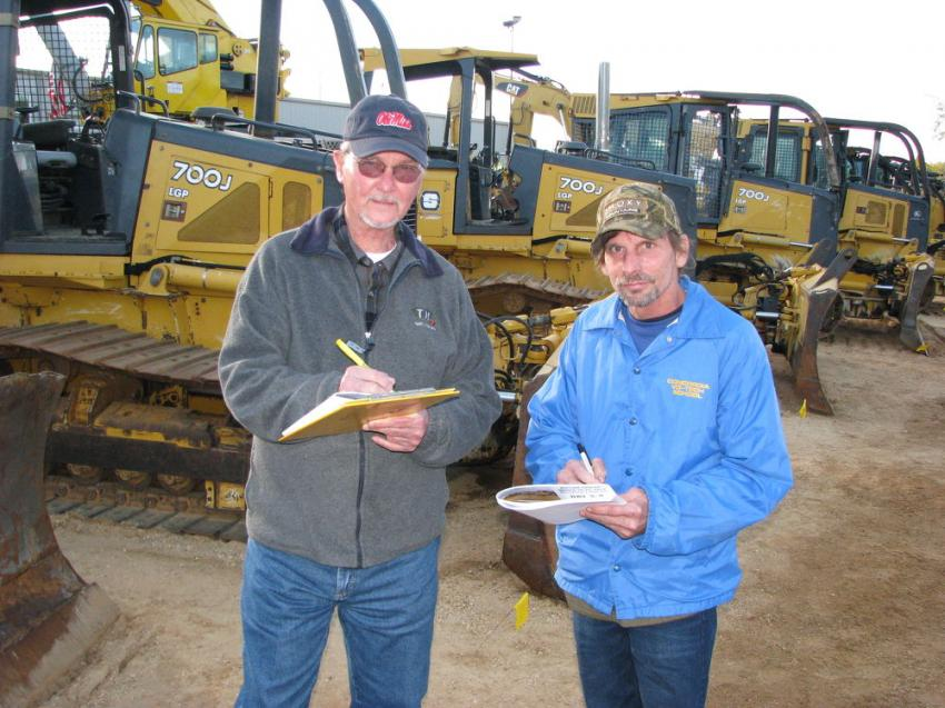 Jotting notes on some of the machines about to be sold are John McClendon (L) and Gary Butler of McClendon Farm Equipment Sales, Houlka, Miss.