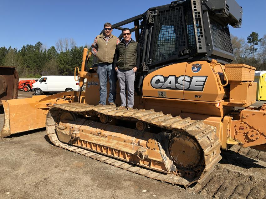 Robbie Ervin (L) and Dru Dunois, both of Hills Machinery, watched the attendees' interest and bidding on a Case 1650C dozer.