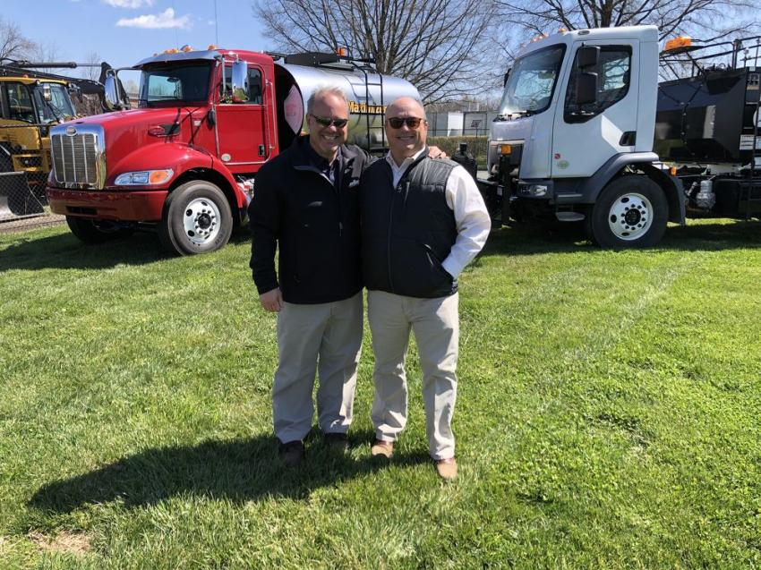 Bryce Davis (L) of LeeBoy and Kenny Bishop of Ascendum stand in front of a LeeBoy distributor truck.