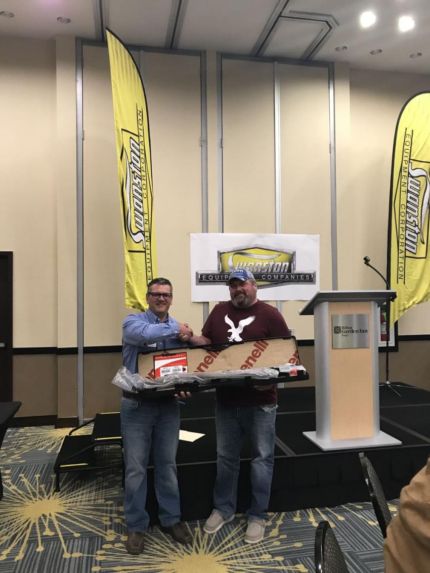 Chris Shea (L), vice president of Swanston Equipment, presents David Uhlenkamp of Mayo Construction with the new 2019 Benelli Super Black Eagle 3 he won in the Grand Finale raffle.