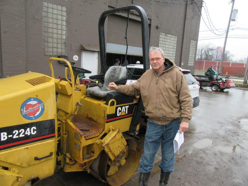 Mark Szakacs Sr., president of Marks Construction, inspects a Caterpillar CB-224C roller at the auction.