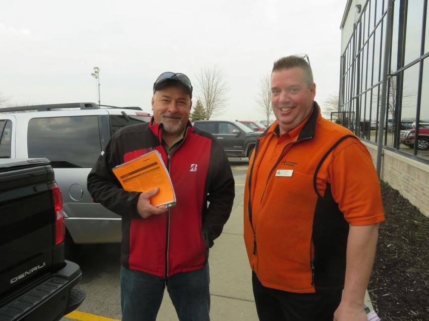 Barry Christian (L) of Construction Resource Management speaks with Ritchie Bros.' Jim Ban.