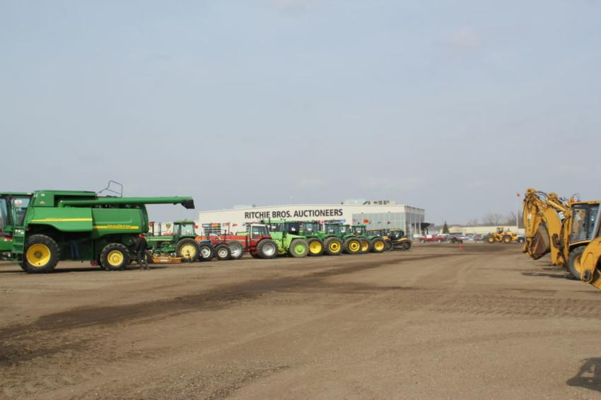 Green equipment is lined up in front of the Ritchie Bros. building, where the bidding was held.