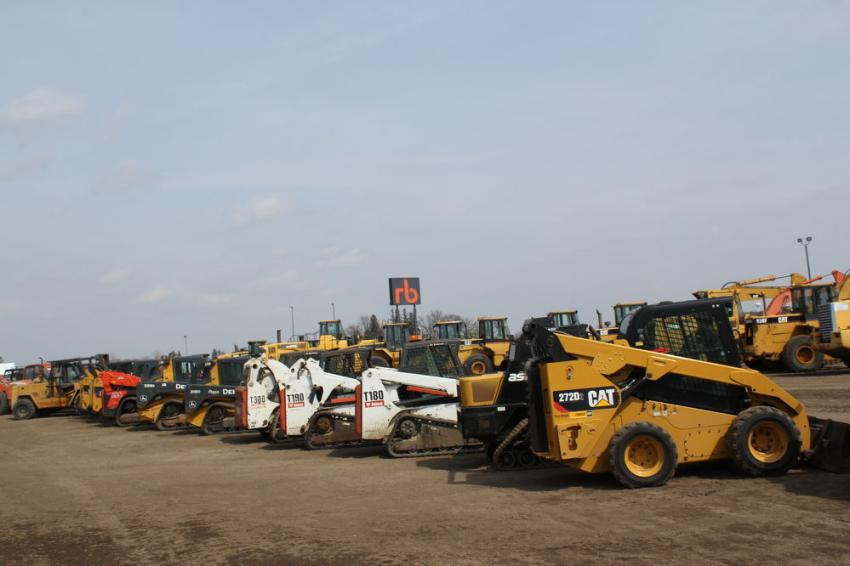 Skid steers and CTLs are lined up on the auction grounds.