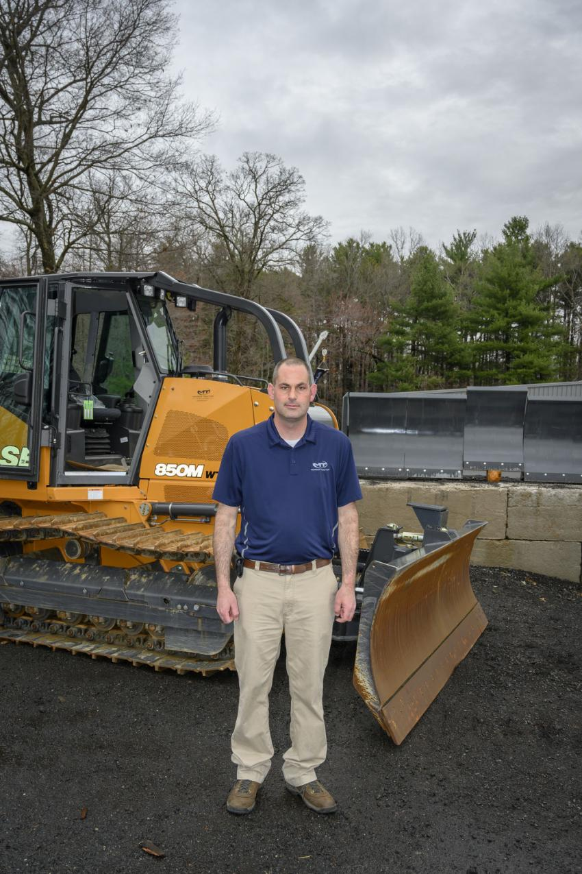 Craig Robbins, Monroe Tractor branch manager, stands in front of a Case 850M dozer at the grand opening of the new facility located at 6 Sandra Drive in South Windsor, Conn.