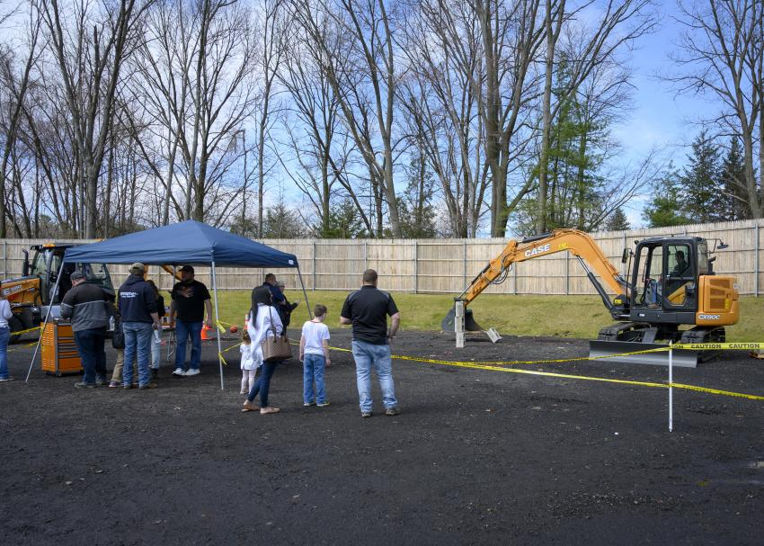 Guests watch as a rodeo competitor stacks the last of the cinder blocks with a Case CX80C Midi excavator.