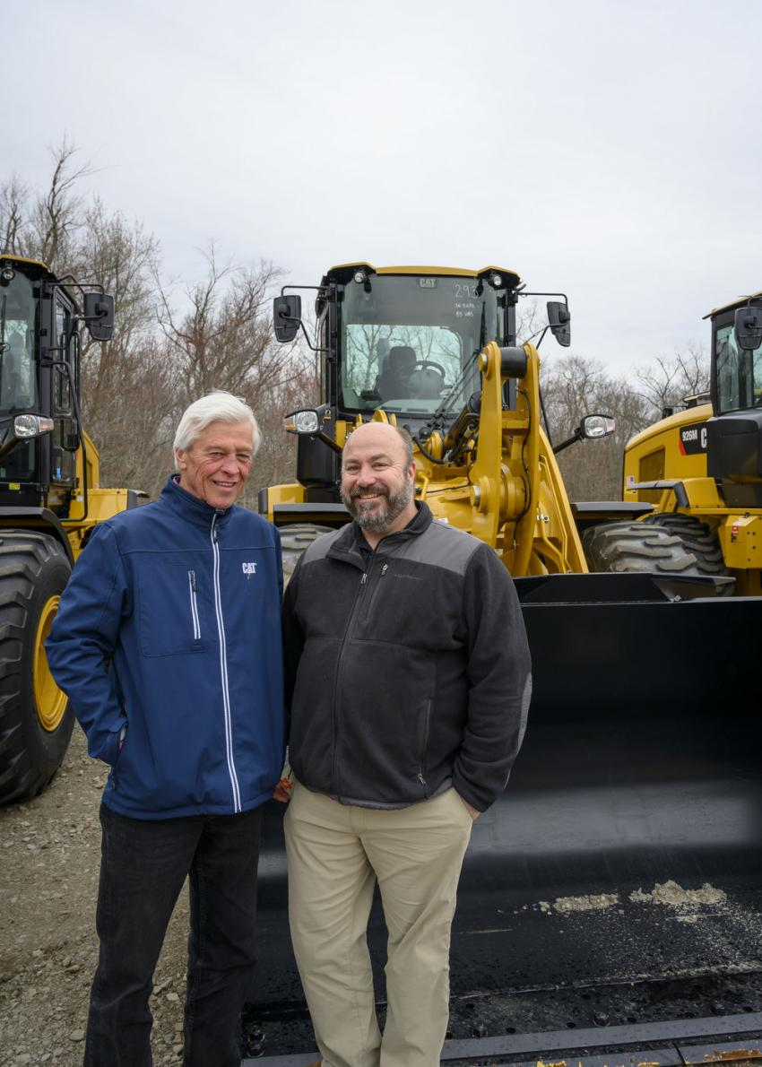 Mike Drewnowski (L) and Erik Sveden, both of Milton CAT in Milford, Mass., stand in front of a 2018 Caterpillar rubber-tired loader.