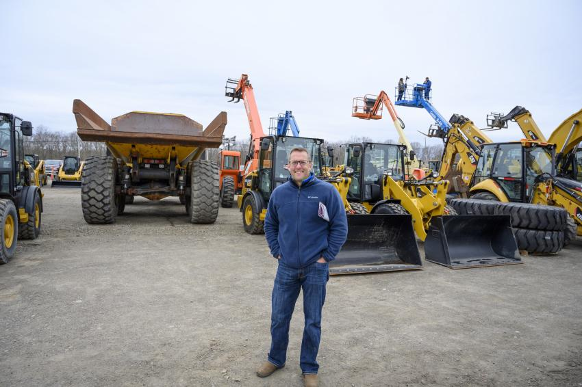 Tim Crean of Crean Equipment in Rutland, Vt., stands in front of several Caterpillar rubber-tired loaders.