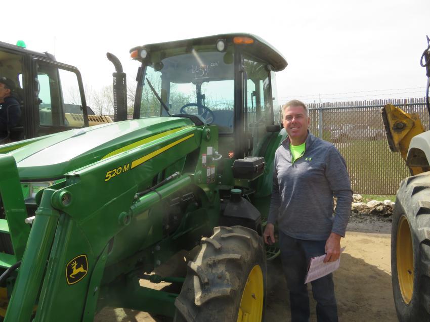 Brian Bruggink of Bruggink Inc. expresses interest in lot No. 454, a 2015 John Deere 520M front loader.