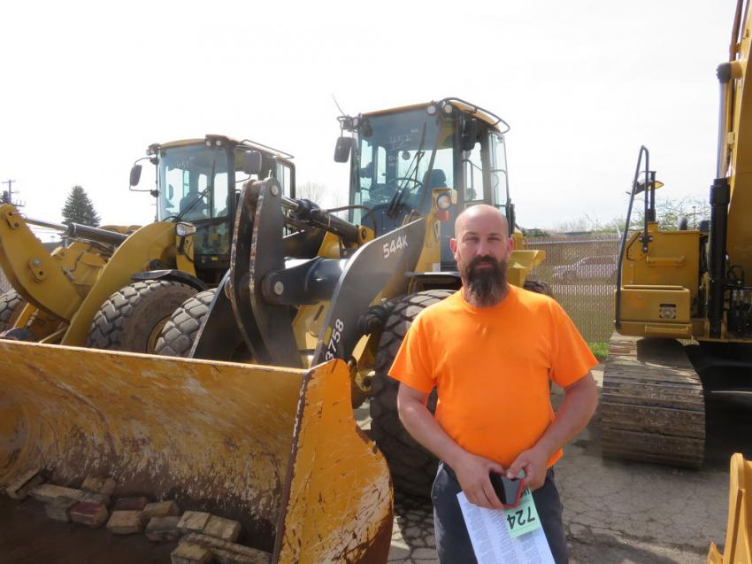Jeremy Feutz of J&M Yard Care checks over a John Deere 544M wheel loader