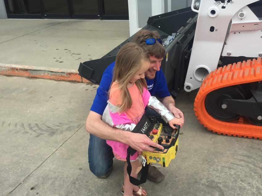 Springfield Branch Manager Kyle Fenski and his daughter, Kylie, operate a Bobcat skid steer by remote control.