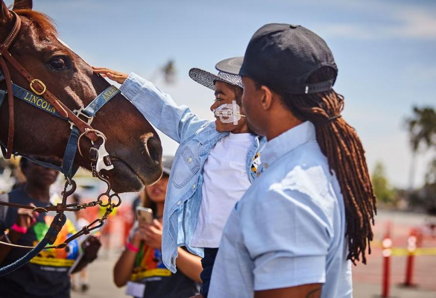 A child reaches out to pet an on-duty horse with the Anaheim, Calif., Police Department.