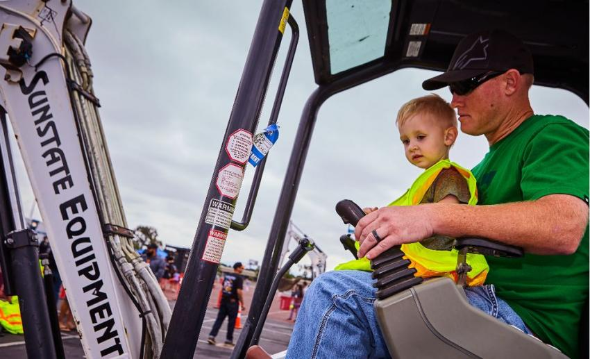 A little boy experiences his first lesson on maneuvering a Bobcat supplied by Sunstate Equipment.
