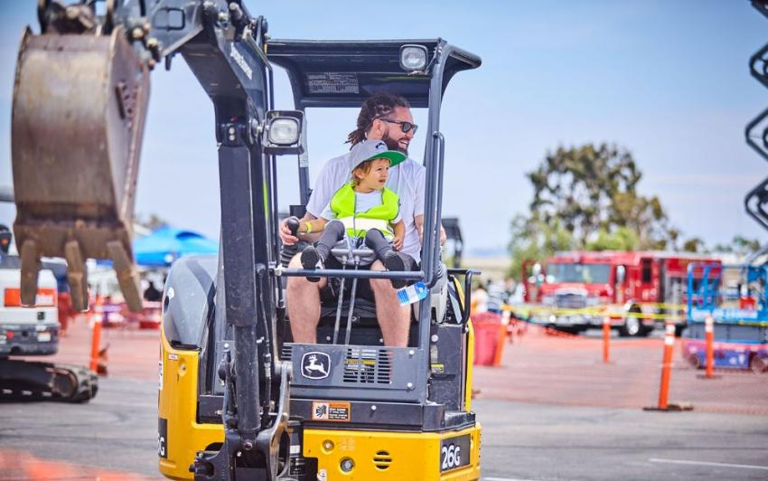 A child is at the controls of a John Deere excavator, courtesy of Sunstate Equipment.