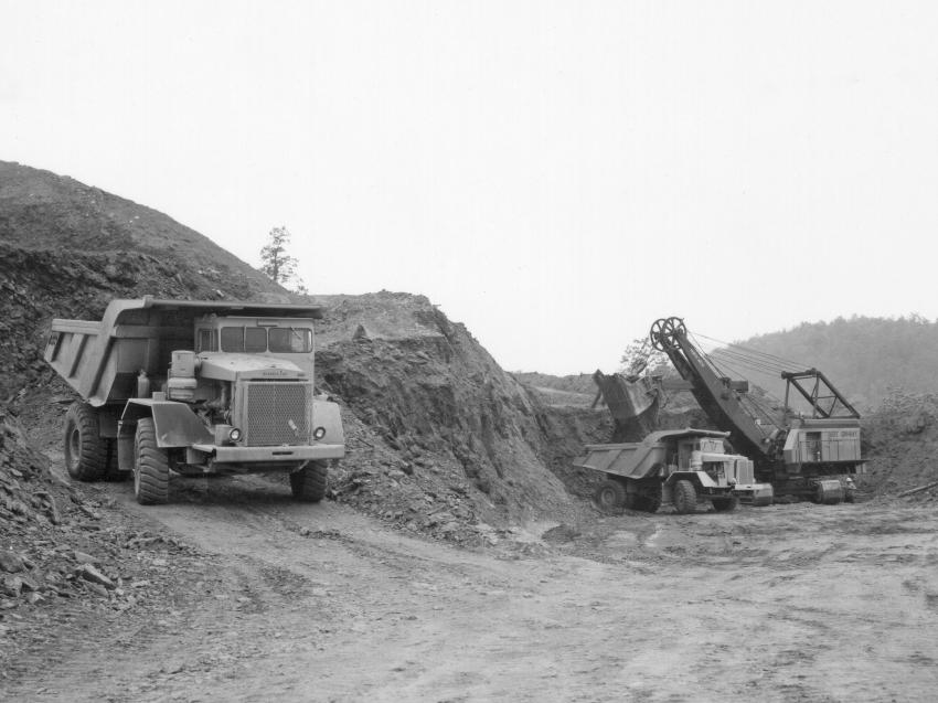A Northwest 180-D shovel with a 4-1/2 cu. yd. dipper loads a fleet of Euclid R-35 rear dump trucks on April 22, 1967. The contractors used a total of five Northwest 180-D shovels on the Carter Dam project to load a fleet of 29 Euclid R-35 trucks. A total of 12.4 million cu. yds. of rock and 1.8 million cu. yds. of earth were moved. (HCEA: Euclid Collection photo)