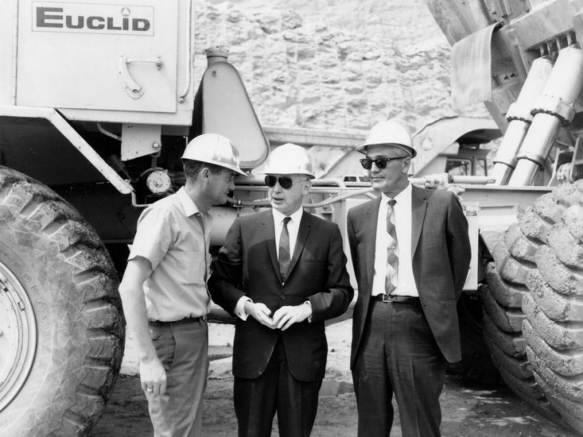 Three unidentified project officials are photographed in front of one of the Euclid R-35 trucks.